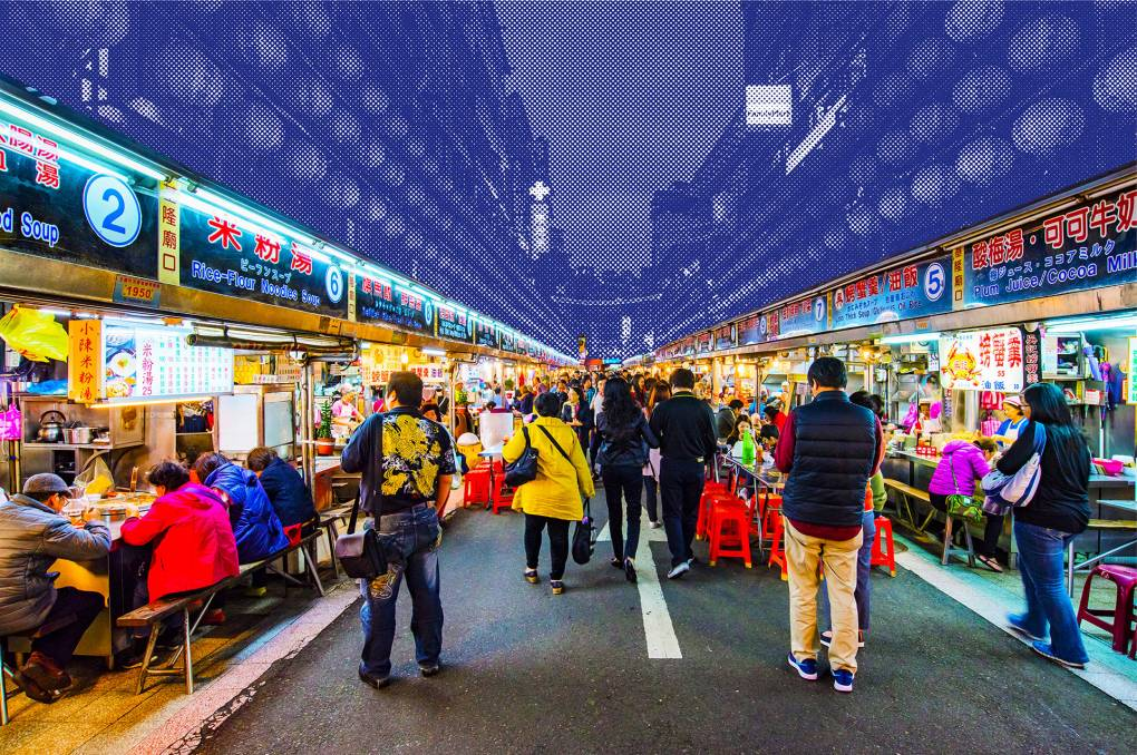 A crowded night market in Taiwan lined with brightly lit food stalls.
