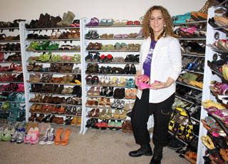 Principal Michele Miller stands with her 375 pairs of shoes.