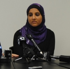 Hani Khan speaks at a press conference announcing her lawsuit.