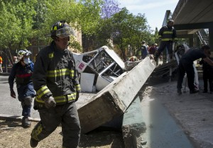 A firefighter walks near a bus damaged by a bridge which collapsed following a strong quake in Mexico. (Ronaldo Schemidt/AFP/Getty Images)