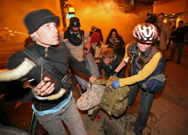 Occupy Oakland protesters carry injured former Marine Scott Olsen after he was struck in the head with a tear-gas canister during unrest in October 2011. Olsen has a lawsuit pending against the city, which settled a suit with a second veteran, Kayvan Sabeghi, for $645,000. (Kimihiro Hoshino/AFP/Getty Images)