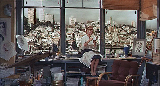"""Scotty visits his old flame Midge (Barbara Bel Geddes).  The vista from her apartment window looks west to Russian Hill from the top of Union Street on Telegraph Hill.  The building on the skyline to the left of Midge's shoulder is the La Mirada apartment building at 1100 Union Street.  This scene was filmed in a studio using a photograph to virtually set the location."" (Courtesy Reel SF)"