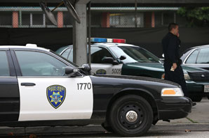 An Oakland Police officer walks by patrol cars at the Oakland Police headquarters. (Justin Sullivan/Getty Images)