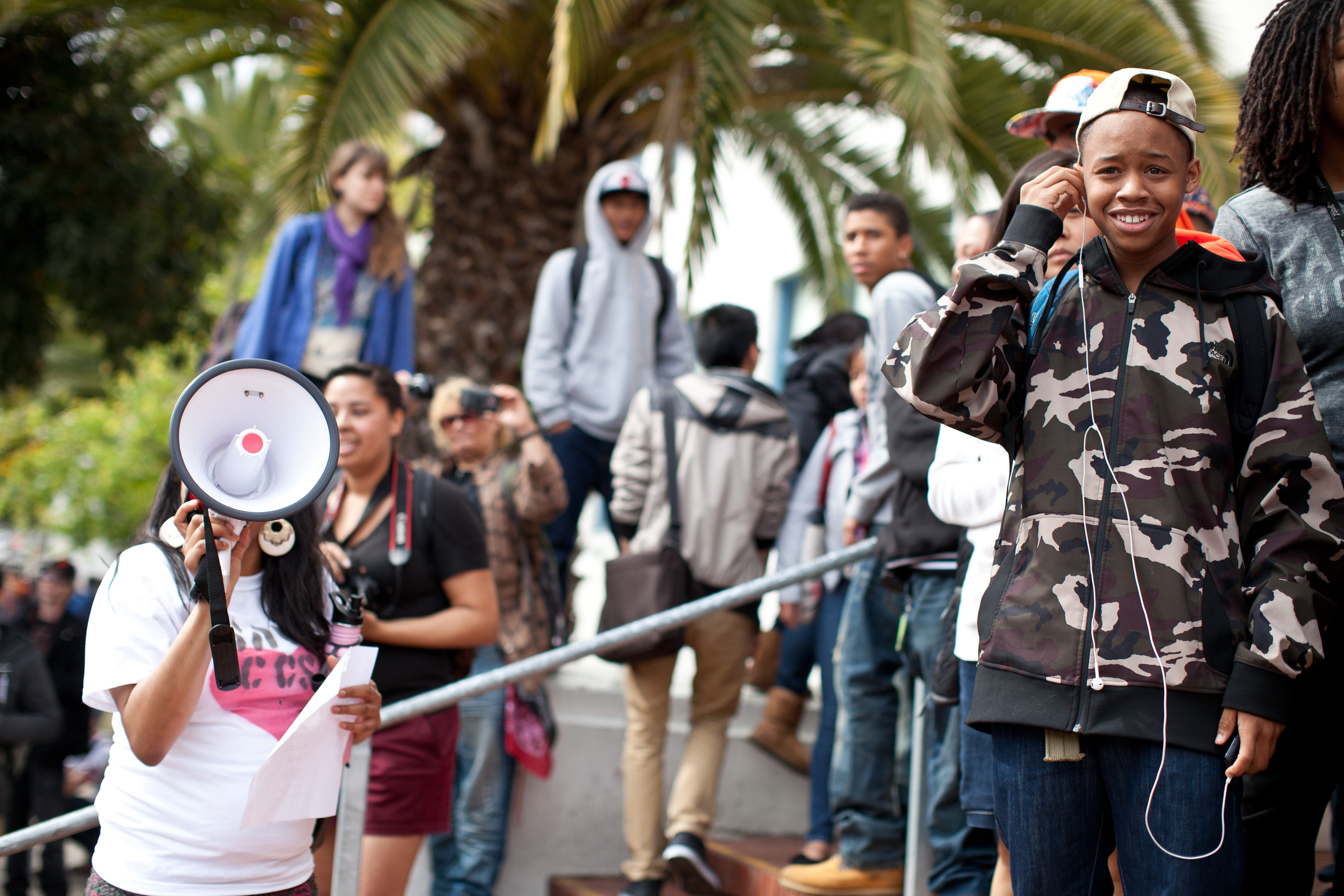 Students from City College campuses marched to Mission High school, where they stood on the sidewalk and encouraged Mission High school students to join them on their march to city hall. Here Rashon Sturdivant, a City College student uses a bullhorn to explain to high school students that their future is at risk, students on the steps are contemplating joining the march and several do. (Deborah Svoboda/KQED)