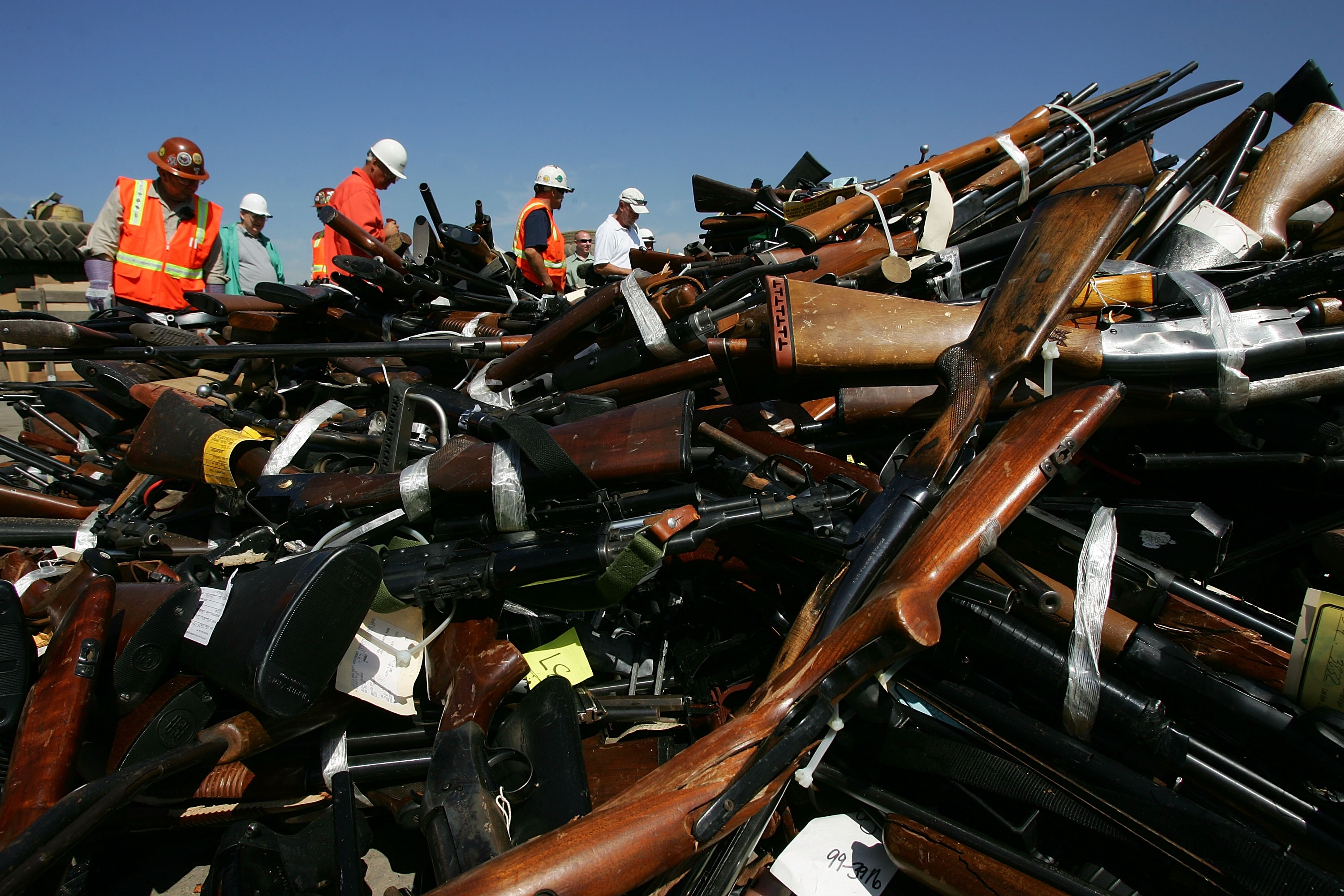 Steel workers look over a pile of more than 4,300 confiscated illegal weapons about to be melted down during the 14th Annual Gun Destruction program. (David McNew/Getty Images)