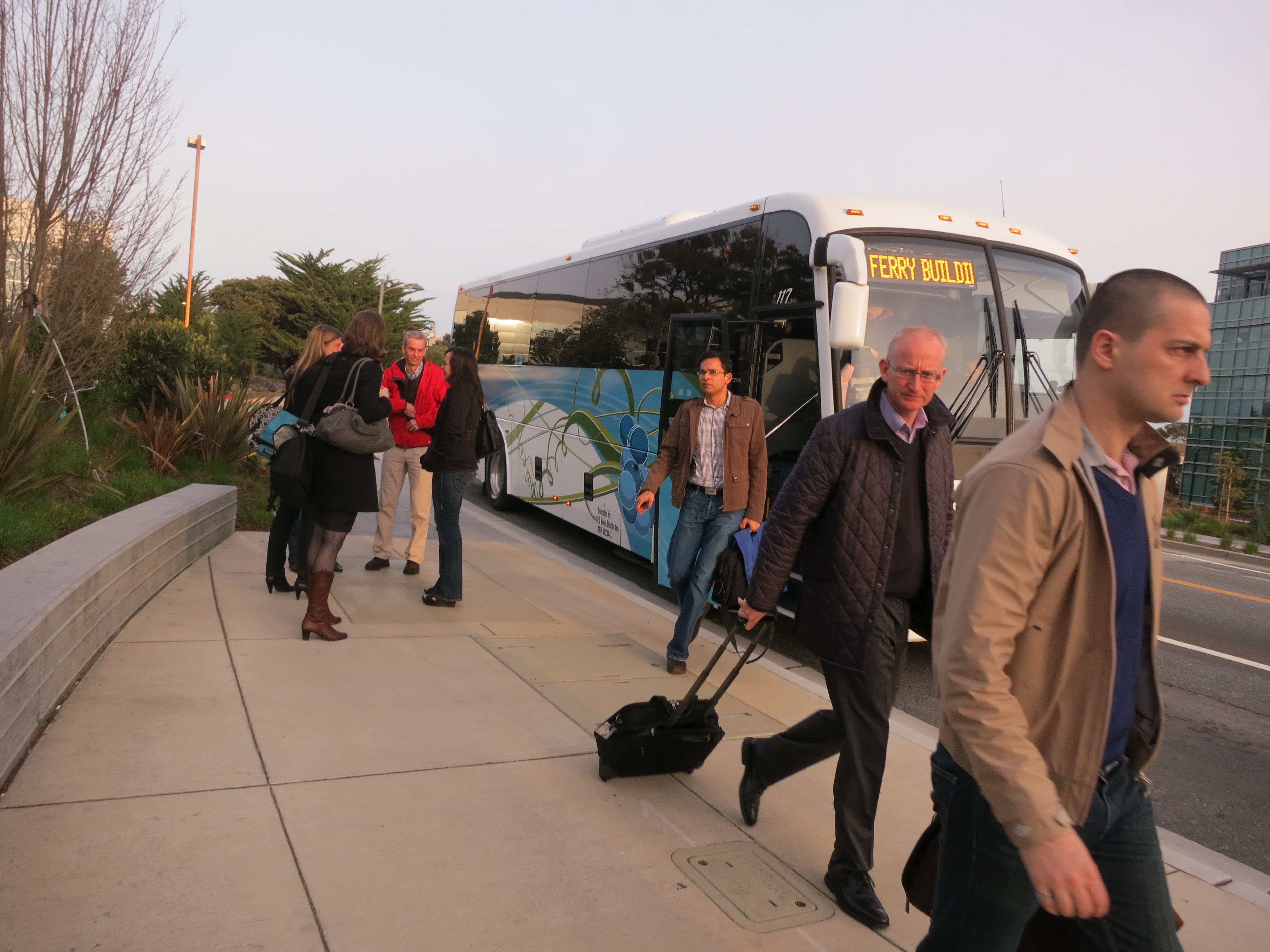 """Genentech employees alight from one of the company's """"gene buses"""" after arriving at work in South San Francisco."""