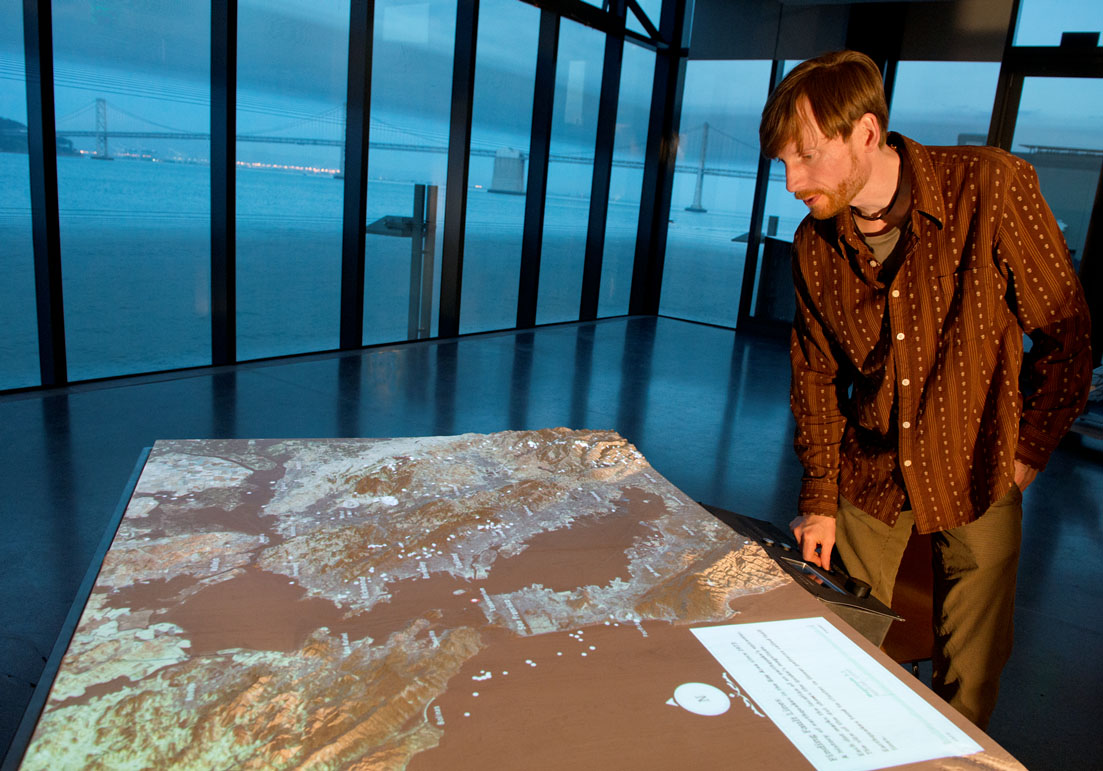Exploratorium scientific content developer Sebastian Martin and an interactive map of the Bay Area in the Bay Observatory.