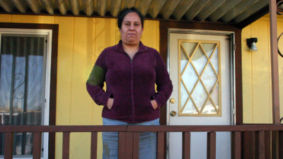 Guadalupe Chavez, standing in front of her mobile home, filed one of the few criminal cases by a California farmworker against a farm supervisor for sexual assault. (Grace Rubenstein/KQED)