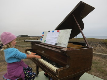 Six-year-old Penelope Keep performs at Francis Beach in Half Moon Bay on one of twelve old pianos that artist Mauro Fortissimo hauled out to the beaches of San Mateo County. (Francesca Segrѐ/ KQED)
