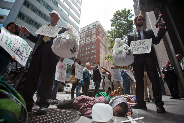 As part of a national day of action against border militarization, faith leaders, workers and community groups held a protest and dramatazation of migrant deaths, outside of the office of one of the top six companies that currently profits from U.S Border contracts. Three people laid as though dead, holding crosses with the names of those that they say have died at the hands of U.S. Customs and Border Control. Names of others that have died were also read out loud. In this photo Rev. Craig Scott (left) and Daren Garshelis (right) pretend to be border patrol, while Luz Anguiano pretends to lie dead with an empty water container. (Deborah Svoboda/KQED)