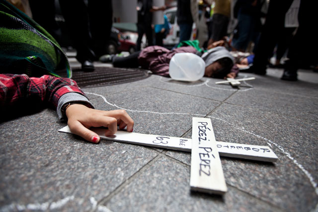 As part of a national day of action against border militarization, faith leaders, workers and community groups held a protest and dramatization of migrant deaths, outside of the office of one of the top six companies that currently profits from U.S Border contracts. Three people laid as though dead, holding crosses with the names of those that they say have died at the hands of U.S. Customs and Border Control. Names of others that have died were also read out loud. (Deborah Svoboda/KQED)
