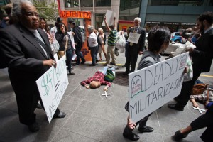 As part of a national day of action against border militarization, faith leaders, workers and community groups held a protest and dramatazation of migrant deaths, outside of the office of one of the top six companies that currently profits from U.S Border contracts. In this photo protesters march around three people pretending to lie dead, representing those that they say have died at the hands of the U.S. Customs and Border Control. Other names of people that they say have died were read out loud. (Deborah Svoboda/KQED)