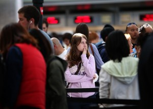 Travelers wait in line to speak with an airline ticket agent at SFO, July 7, 2013. (Justin Sullivan/Getty Images)