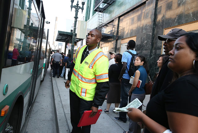 An Alameda-Contra Costa (AC) Transit worker monitors the capacity of an AC Transit bus on July 2, 2013 in Oakland, California. (Justin Sullivan/Getty Images)