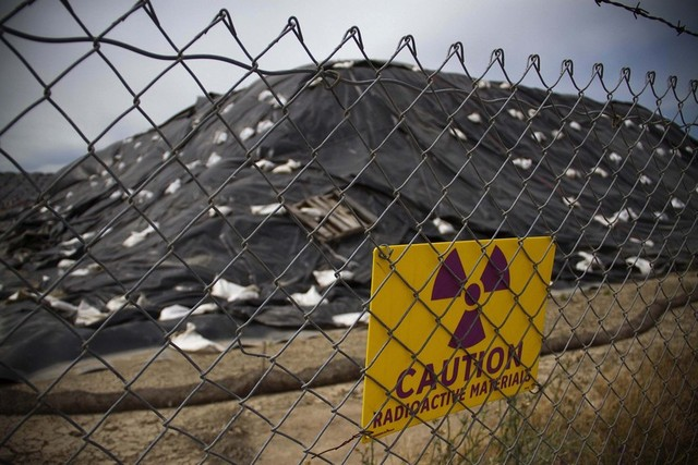 A sign warns of radioactive material around large piles of dirt contaminated with radium at the former McClellan Air Force Base, near Sacramento. (Randy Allen for The Center for Investigative Reporting)