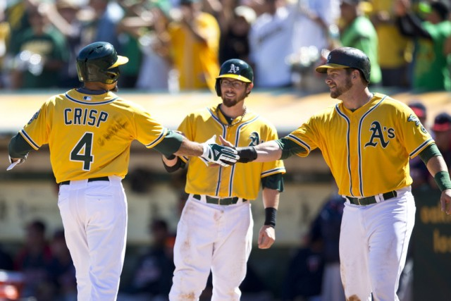 Coco Crisp (#4) of the Oakland Athletics is congratulated by teammates after hitting a three-run home run against the Minnesota Twins during the second inning at O.co Coliseum on September 22, 2013. (Jason O. Watson/Getty Images)