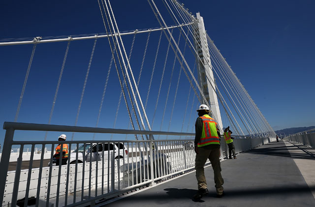 SAN FRANCISCO, CA - AUGUST 26: A worker walks on the bike path next to the new Bay Bridge Self-Anchored Suspension (SAS) tower on August 26, 2013 in San Francisco, California. After nearly 12 years of construction and an estimated price tag of $6.4 billion, the new eastern span of the Bay Bridge is set to open on September 3. The bridge will be the world's tallest Self-Anchored Suspension (SAS) tower once completed. (Photo by Justin Sullivan/Getty Images)