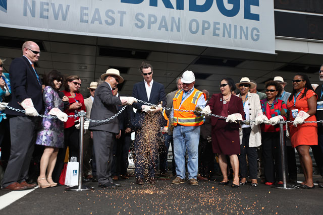 Lt. Gov. Gavin Newsom cuts a chain with a blow torch to ceremonially open the Bay Bridge on Sept. 2. He is flanked by Oakland Mayor Jean Quan and San Francisco Mayor Ed Lee. (Photo by Deborah Svoboda/KQED)