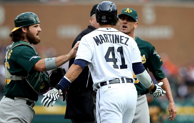 Oakland A's catcher Derek Norris, left, tries to intercede with Victor Martinez of the Detroit Tigers, who took exception to comments from A's pitcher Grant Balfour, right. (Leon Halip/Getty Images)