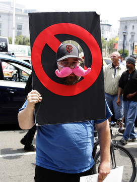 DeSoto Cab Company driver Corey Lamb protests against app-based ride-service companies outside San Francisco City Hall. (Alex Enslie/KQED)