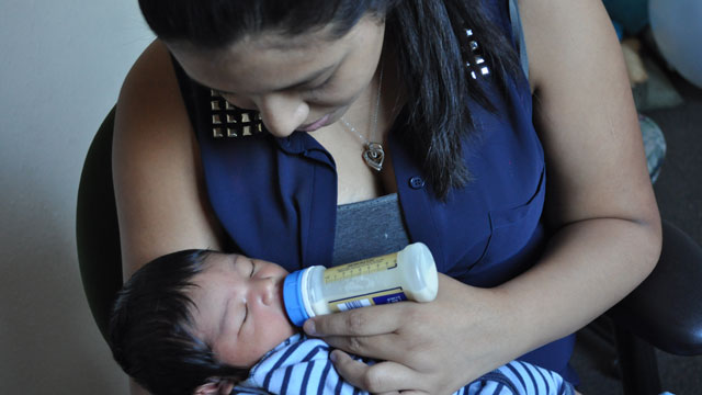 Carretero feeds her infant son. (Marci Lopez/The kNOw at New American Media)