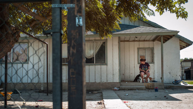 Jessica Ortiz sits on the porch of her home in Raisin City, Calif. (Scott Anger/KQED)