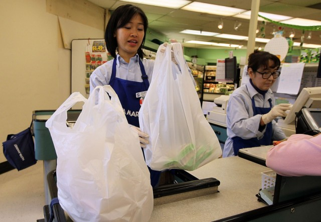 A cashier bags groceries in plastic bags at Nijiya Market June 2, 2010 in San Francisco, California. (Photo by Justin Sullivan/Getty Images)
