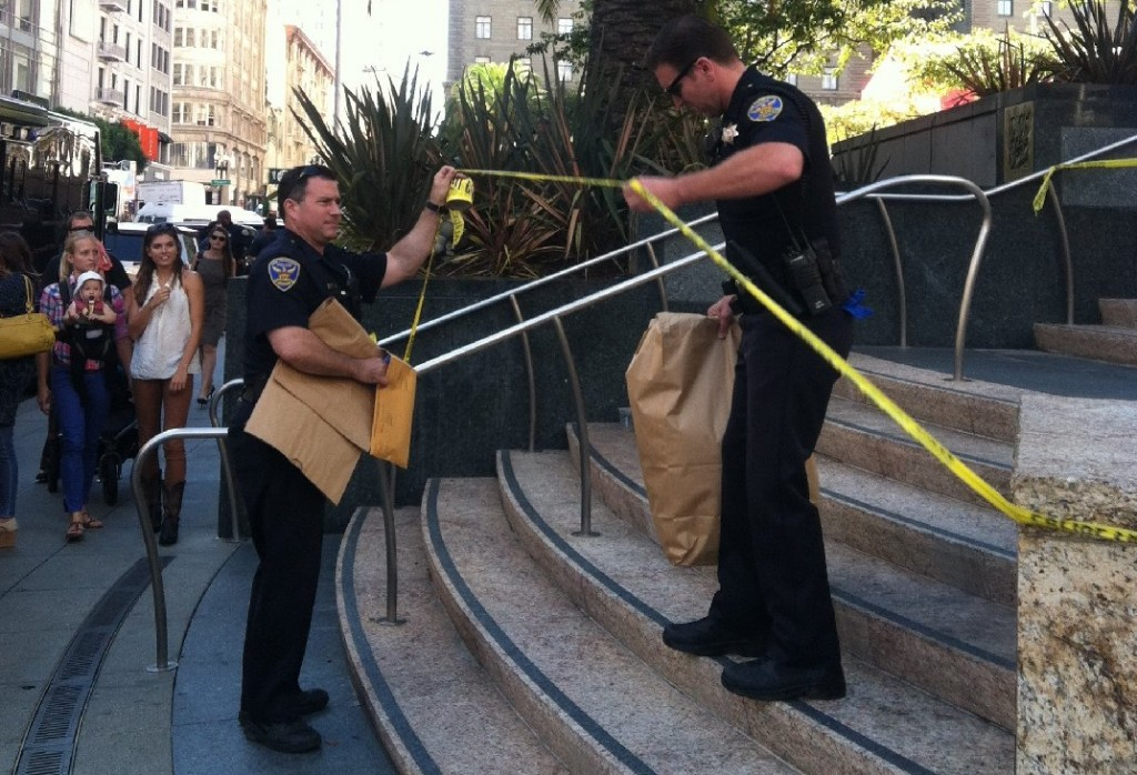 Police officers remove a suspicious package that led to the evacuation of San Francisco's Union Square at midday. (Rachael Marcus/KQED)