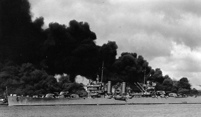 The USS Phoenix steams past battleships burning after attack on Pearl Harbor on Dec. 7, 1941. (U.S. Naval HIstorical Center)