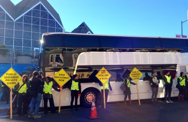 In a December protest, activists surround a Google bus at 24th and Valencia streets Monday in protest aimed at evictions and displacement in San Francisco's Mission District. (Steve Rhodes via Flickr)