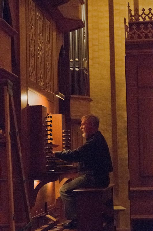 "Fritz Noack works on the final ""voicing"" of the organ."