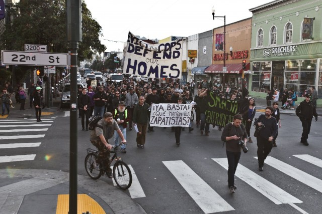 "About 100 protesters and residents welcomed the new year by marching from the 24th Street BART to the 16th Street BART station on New Year's day. They were protesting the police enforcement of evictions and claim the Mission is being turned into ""a playground for the rich."" (Deborah Svoboda/KQED)"