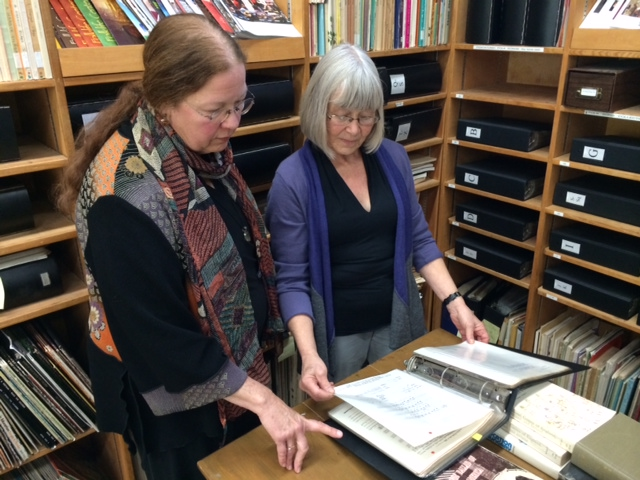Holy Names University Music Lecturer Gail Needleman (left) and Kodály Center Director Anne Lasky pore over the printed originals of some of the folk songs now on the Center's digital archive. (Joshua Johnson/KQED)