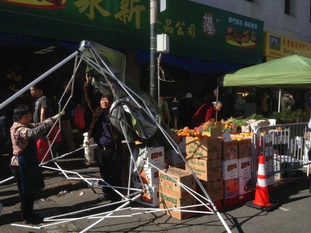 A merchant on Stockton Street tries to set up his stall, but gusts of wind make it a protracted struggle. (Patricia Yollin/KQED)