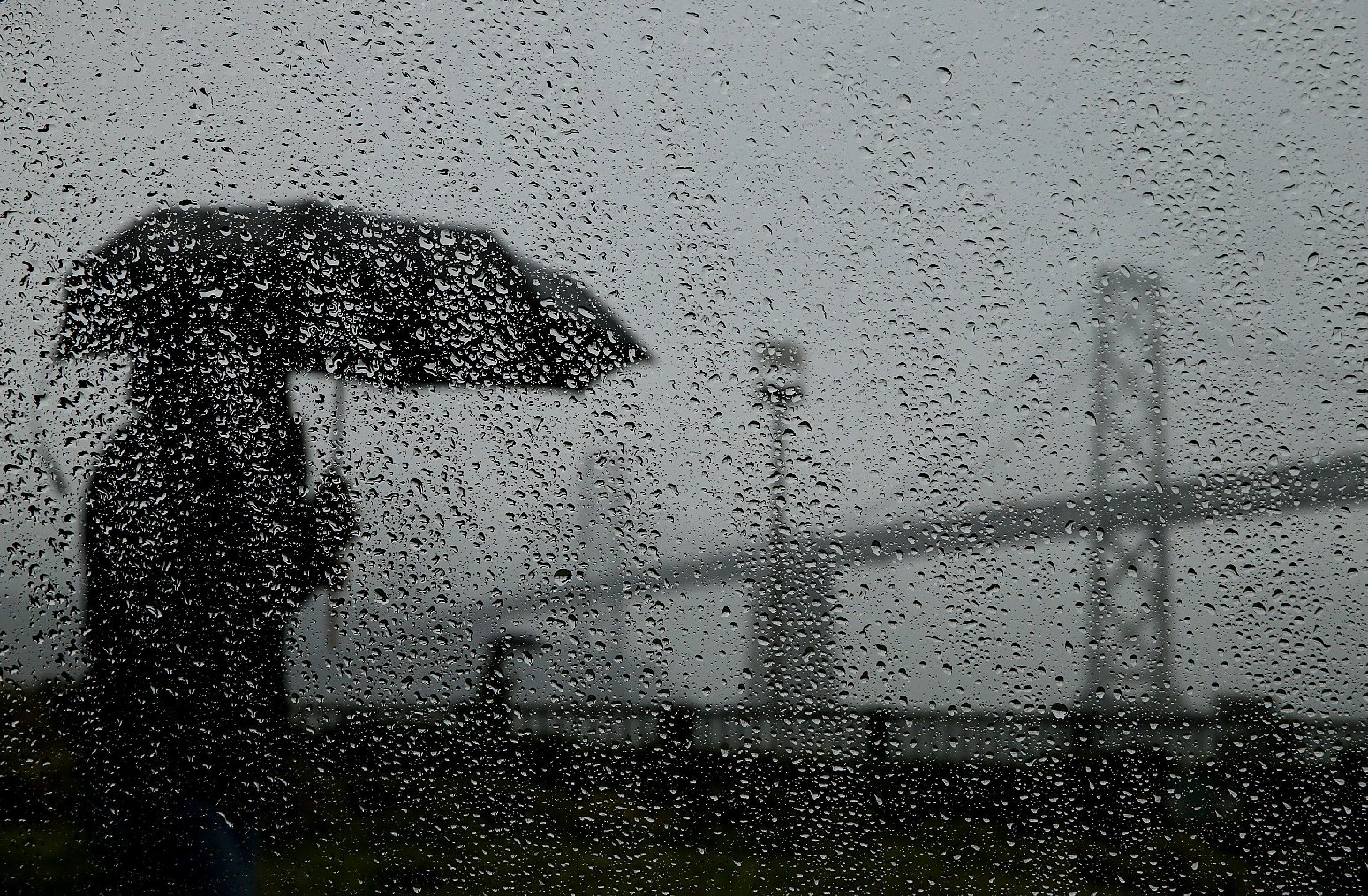 Pedestrian in the rain along San Francisco's Embarcadero during Bay Area's first major storm of 2014. (Justin Sullivan/Getty Images)