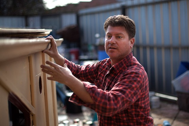 Kloehn fits a wooden gutter on the exterior of a tiny house he refers to as the 'Uni-bomber Shack.' (Mark Andrew Boyer/KQED)