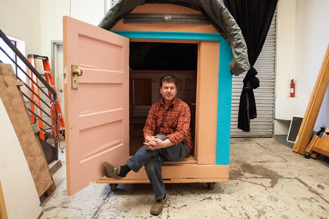 Artist and designer Gregory Kloehn sits in the doorway of his latest tiny house, which he calls the Chuckwagon. (Mark Andrew Boyer/KQED)