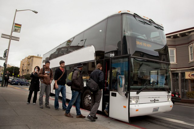 Workers board a private bus at 24th and Valencia streets. (Mark Andrew Boyer/KQED)