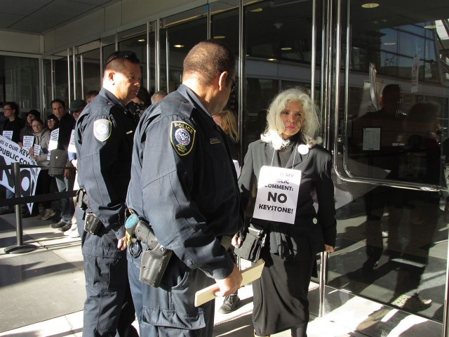 An activist blockading the Federal Building is detained by Police. (Jack Detsch/KQED)