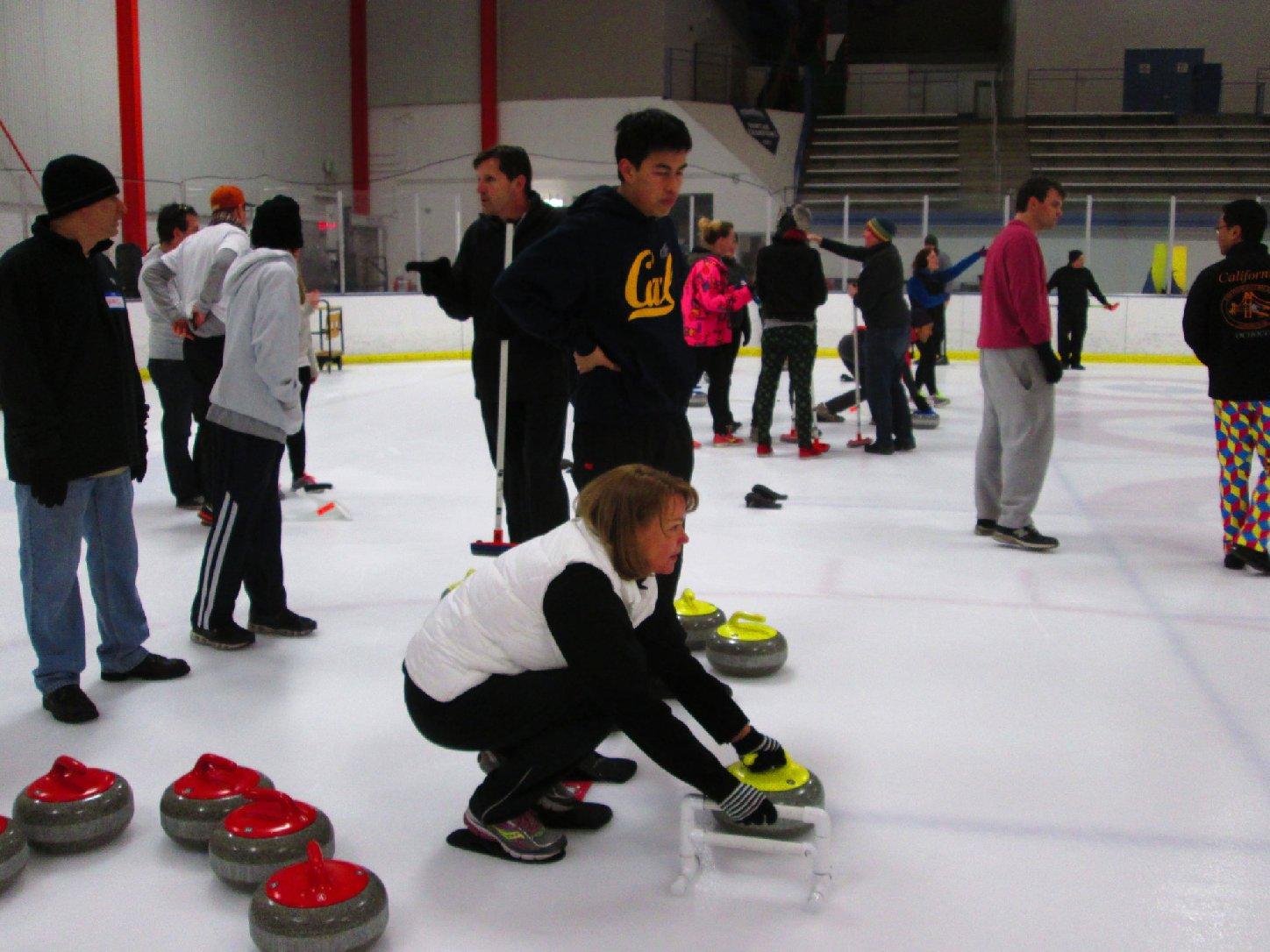 Bay Area Curling Club instructor Joseph Tang shows aspiring curler Nancy Carruth of San Francisco the basics at the Oakland Ice Arena on Feb. 1, 2014. (Nina Thorsen/KQED)