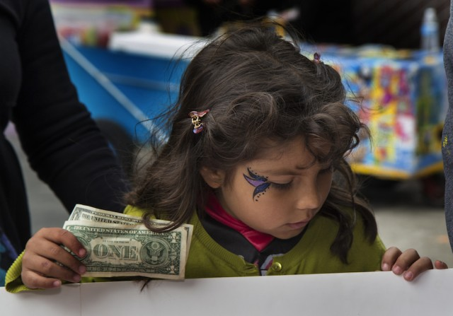 A child buys tickets at the Halloween-Día de los Muertos fundraiser for Junipero Serra Elementary in Bernal Heights. The event netted $3,000 for the PTA. (Tearsa Joy Hammock / San Francisco Public Press)