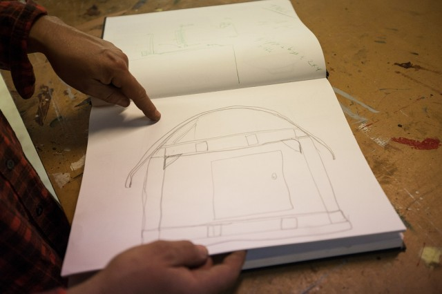 Kloehn shows off sketches of some of his previous tiny homes. (Mark Andrew Boyer/KQED)