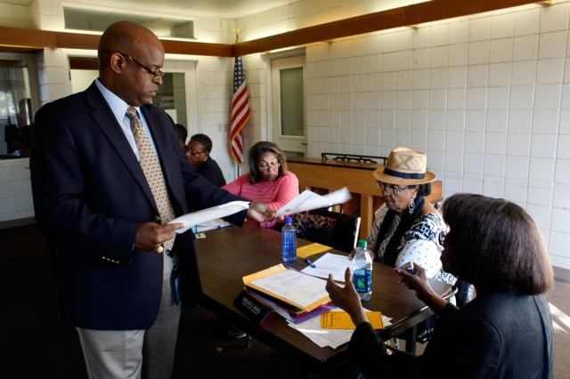 Richmond Housing Authority Executive Director Tim Jones hands out copies of notes from a previous meeting to residential council leaders from the city's public housing properties. Jones blames years of federal funding cuts for the problems plaguing the authority. (Lacy Atkins/San Francisco Chronicle)