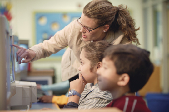 A teacher helps students at computers. (ThinkStock/Getty Images)