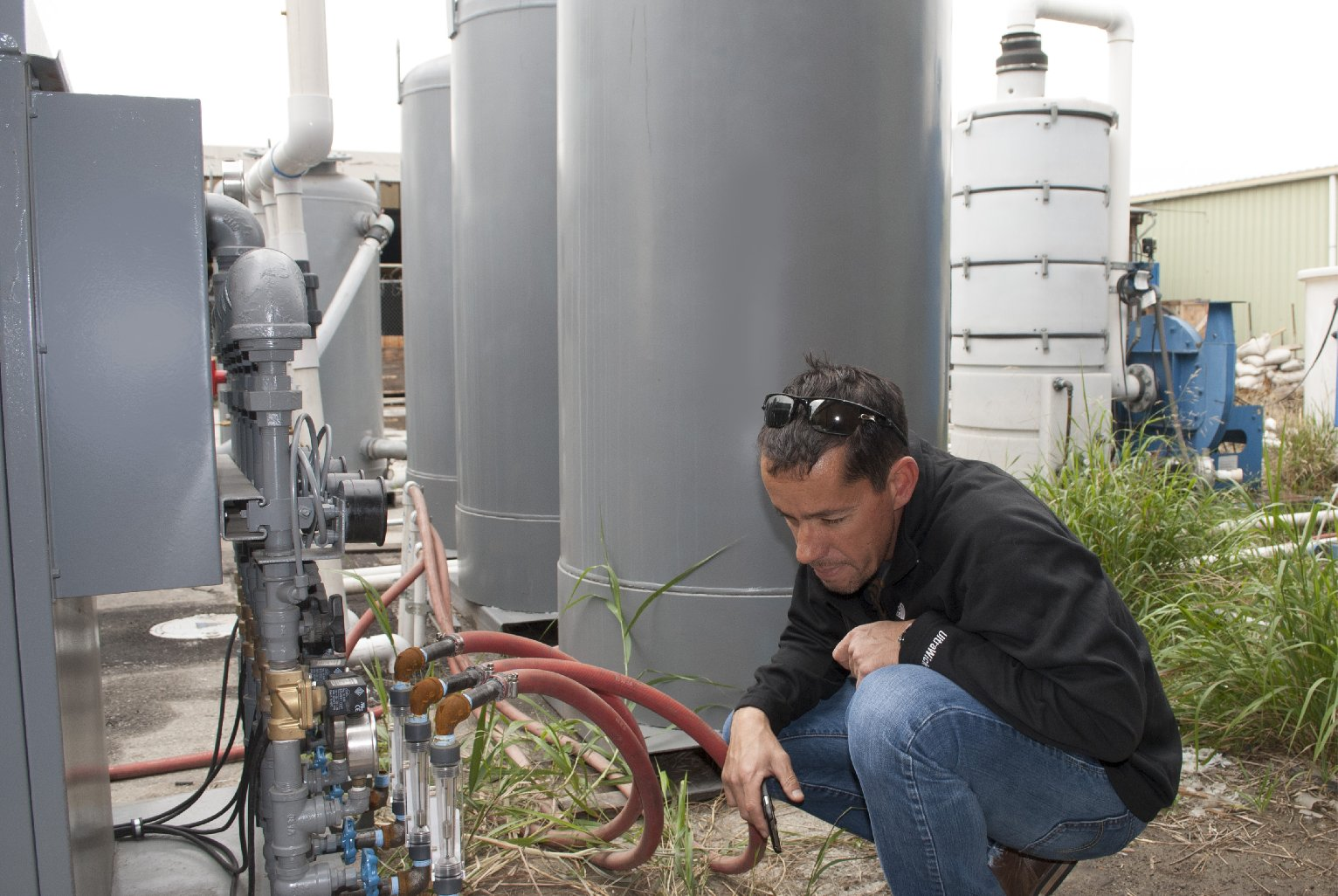"""Wayne Ziegler, general manager of the environmental remediation company The Reynolds Group, checks """"sparging"""" equipment at a cleanup site south of Los Angeles. (Chris Richard/KQED)"""