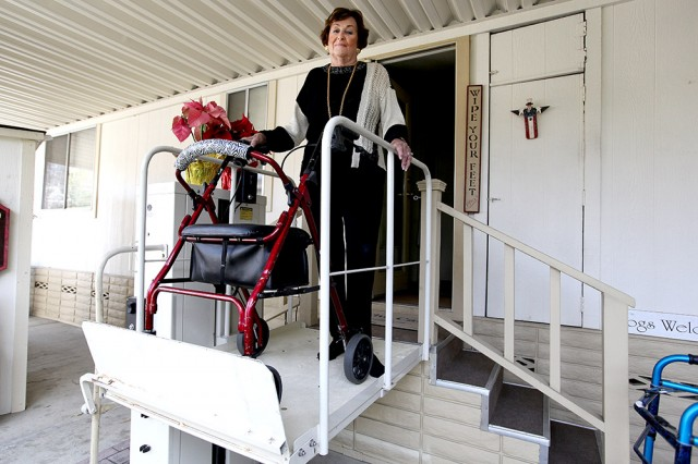 Barbara Cali, co-founder and resident of Winchester Ranch, stands on the lift at the entrance of her home. (Mark Andrew Boyer/KQED)