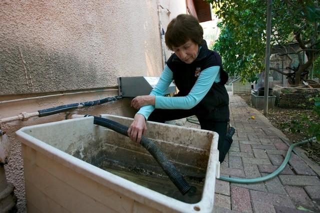 Reporter Francesca Segré's aunt, Amelia Terkel, tends her graywater system in Herzliya, Israel. (Francesca Segrè/KQED)