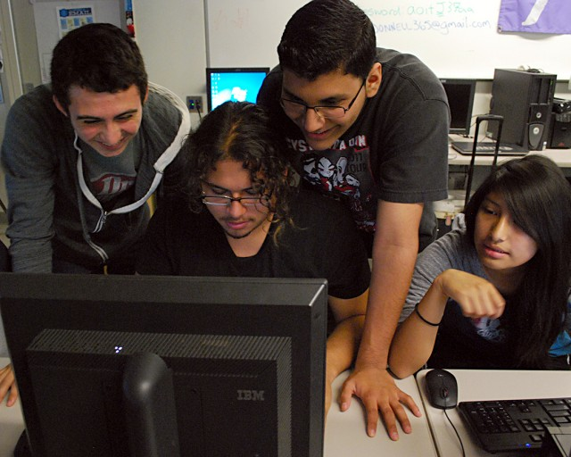 Joe Sanbria (seated) gets help from his classmates with the programming language Python at Foshay Technology Academy in Los Angeles. (Lillian Mongeau,/EdSource Today)