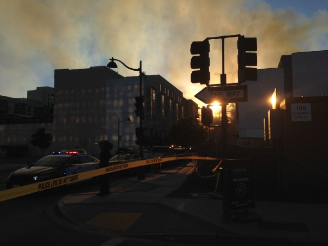The sun sets, highlighting the smoke from the 5-alarm fire. (Jeremy Raff/KQED)