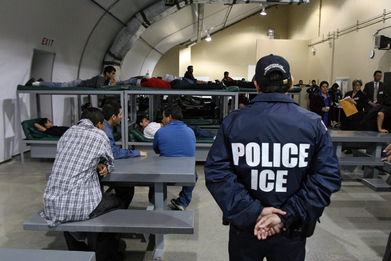 An Immigration and Customs Enforcement officer guards a group of 116 Salvadorean immigrants that wait to be deported,at Willacy Detention facility in Raymondville, Texas. (Jose Cabeza/AFP/Getty Images)